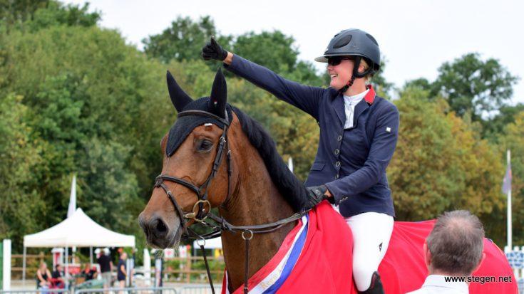 Renate Beuving steekt haar duim omhoog richting haar fans, nadat ze met Fellow Drents kampioen ZZ-springen is geworden.