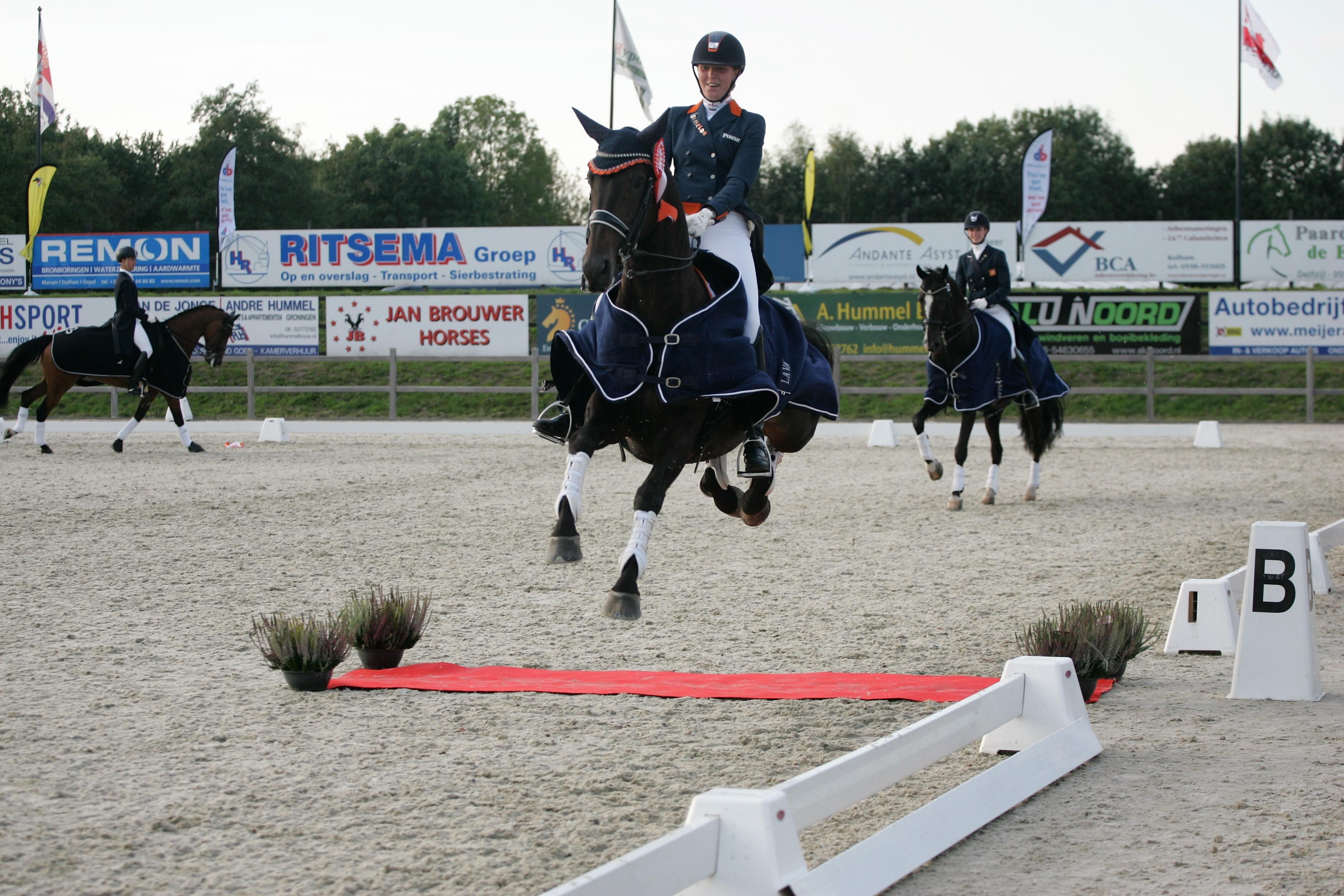 Diana van de Bovenkamp springt met dressuurpaard Evita Ronia over de rode loper.