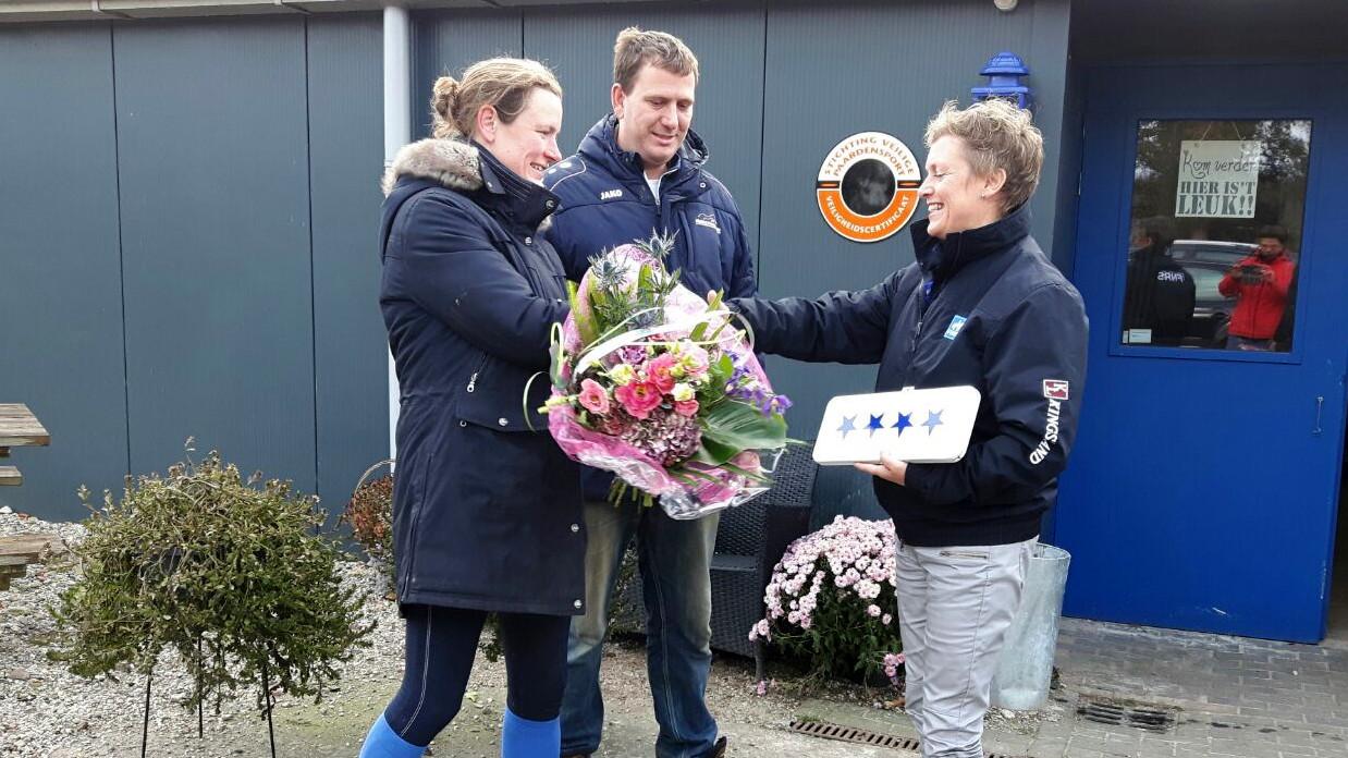 Hippisch Centrum Eelde. Swaen Brink van de FNRS overhandigt de vierde ster aan broer en zus Arjan en Karlijn van Vugt van het hippisch centrum Eelde.